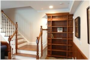 Hidden bookcase door at bottom of stairs