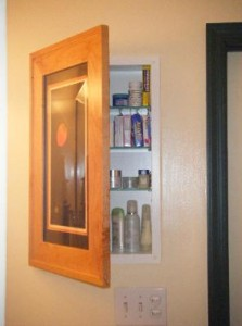Hidden medicine cabinet behind picture frame