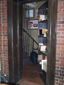 Hidden swing-in bookcase door reveals hidden stairs