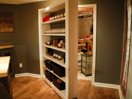 Secret bookcase door for storage closet stashvault for Hidden storage ideas