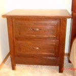 Bedside table with hidden compartment drawer behind bottom panel